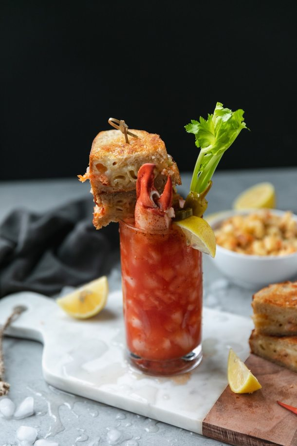 Shot of a bloody mary garnished with a grilled cheese sandwich on a skewer and a lobster claw sticking out of the drink with a lemon wedge and celery stalk with a bowl of mac and cheese behind it and a grilled cheese sandwich next to it