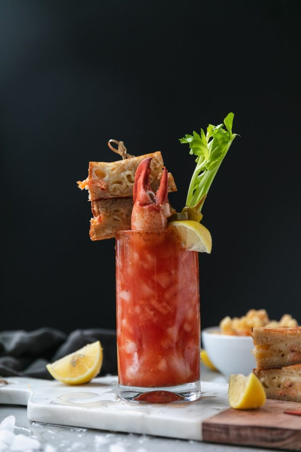 Forward facing shot of a bloody mary garnished with a grilled cheese sandwich on a skewer and a lobster claw sticking out of the drink with a lemon wedge and celery stalk with a bowl of mac and cheese behind it and a grilled cheese sandwich next to it