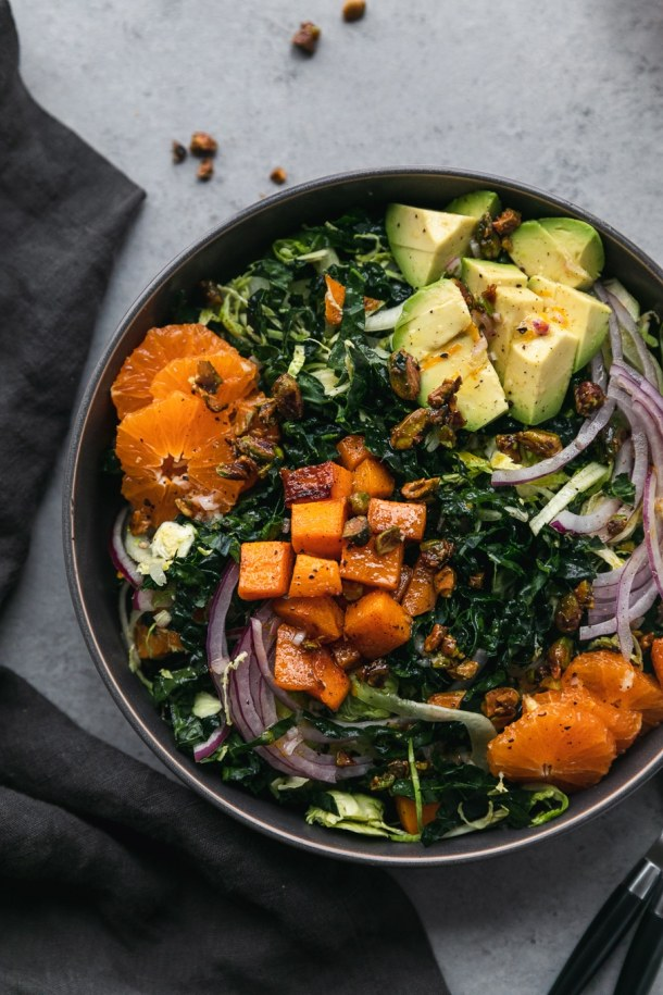 Overhead close up shot of a kale salad with avocado, mandarins, red onion, butternut squash, and candied pistachios with a dark grey napkin next to it