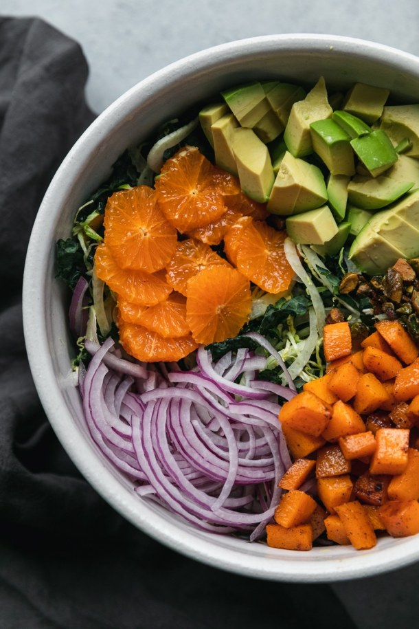 Overhead close up shot of a salad bowl filled with kale, brussels, mandarins, red onion, avocado, roasted butternut squash, and candied pistachios