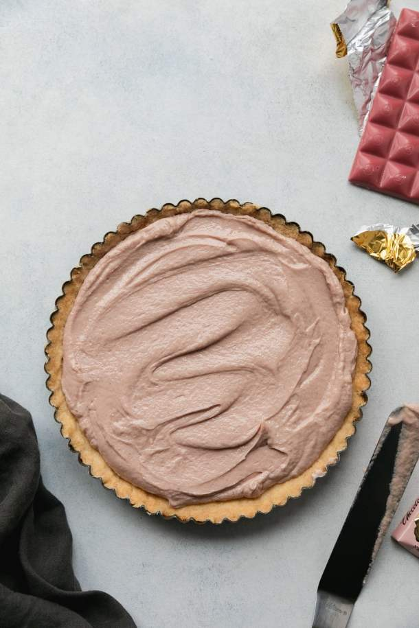 Overhead shot of a cheesecake tart with a pink chocolate bar in gold wrapper in the top right of the frame