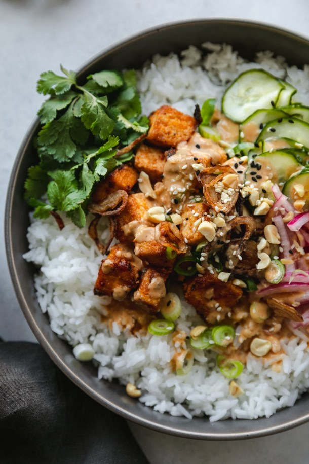 Overhead close up shot of a rice bowl topped with tofu, pickled vegetables, and cilantro