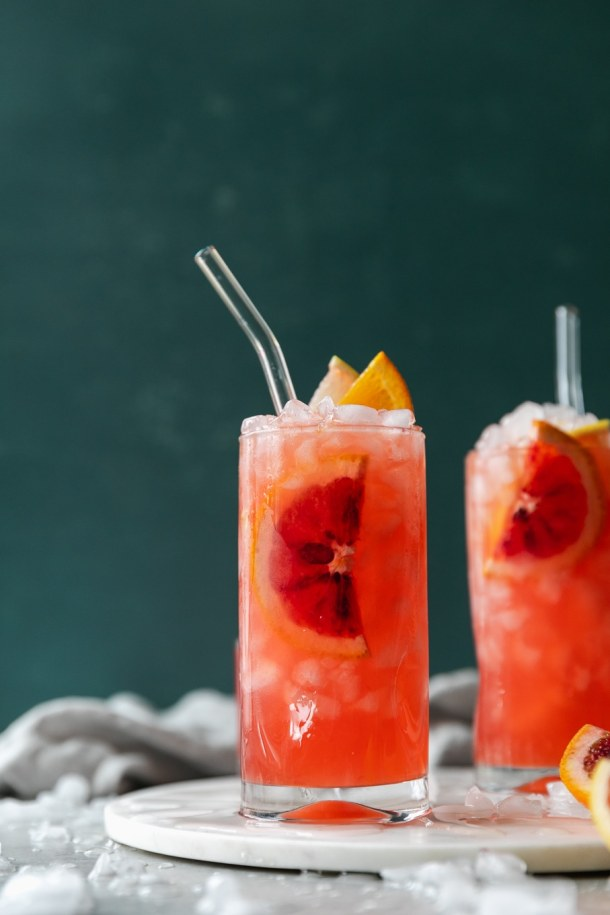 Forward facing shot of two pink winter citrus crush cocktails garnished with sliced blood orange, tangelo, and a clear glass straw against a dark blue background