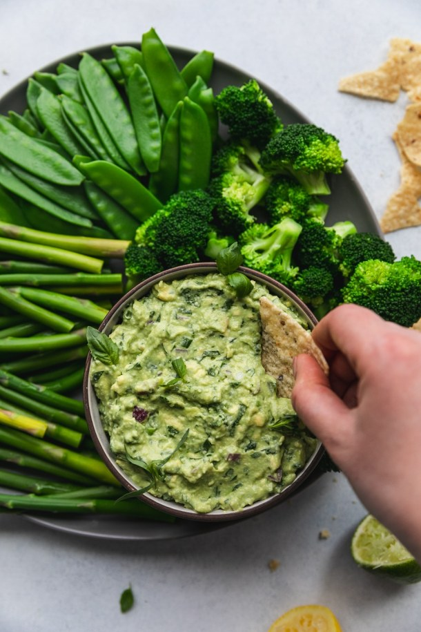 Overhead shot of a hand dipping a chip into green goddess guacamole with asparagus, snow peas, and broccoli around the bowl