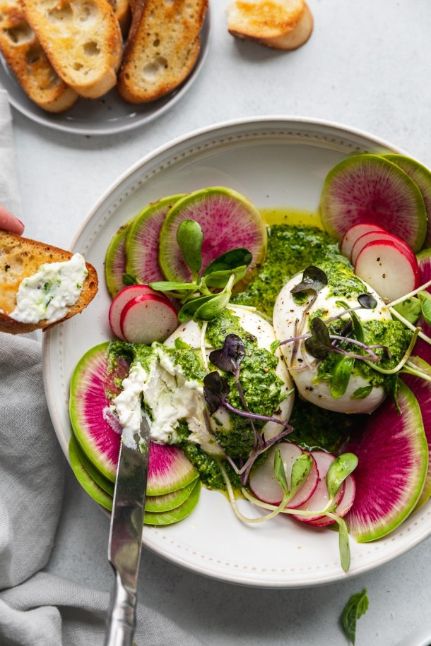 Overhead shot of green goddess pesto burrata being spread on a crostini with watermelon radishes and micro greens garnishing the bowl