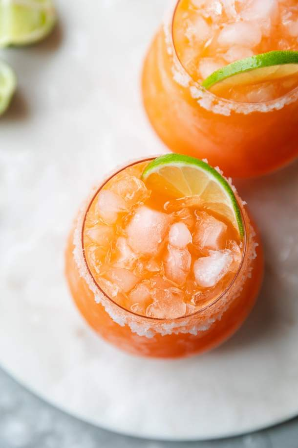 Overhead close up shot of a carrot ginger margarita garnished with a lime slice