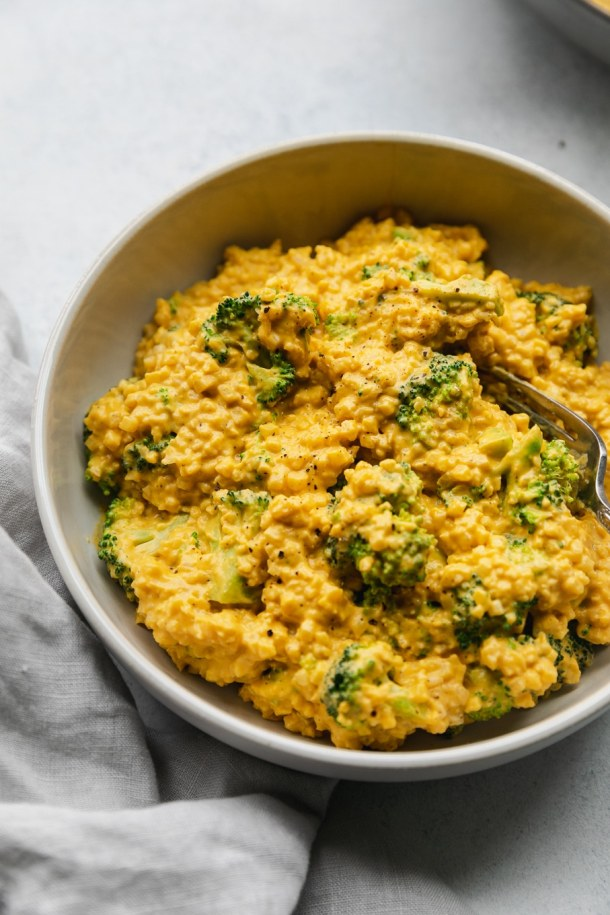 Close up shot of a bowl of cheesy vegan broccoli cauliflower rice