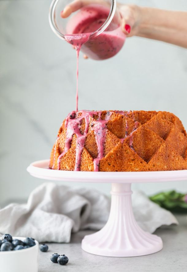 Forward facing shot of a lemon pound cake being drizzled with blueberry glaze on a pink cake stand