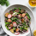 Overhead shot of a large white bowl filled with roasted potato salad with asparagus, sliced radishes, red onion, and fresh herbs with a silver spoon resting in the bowl