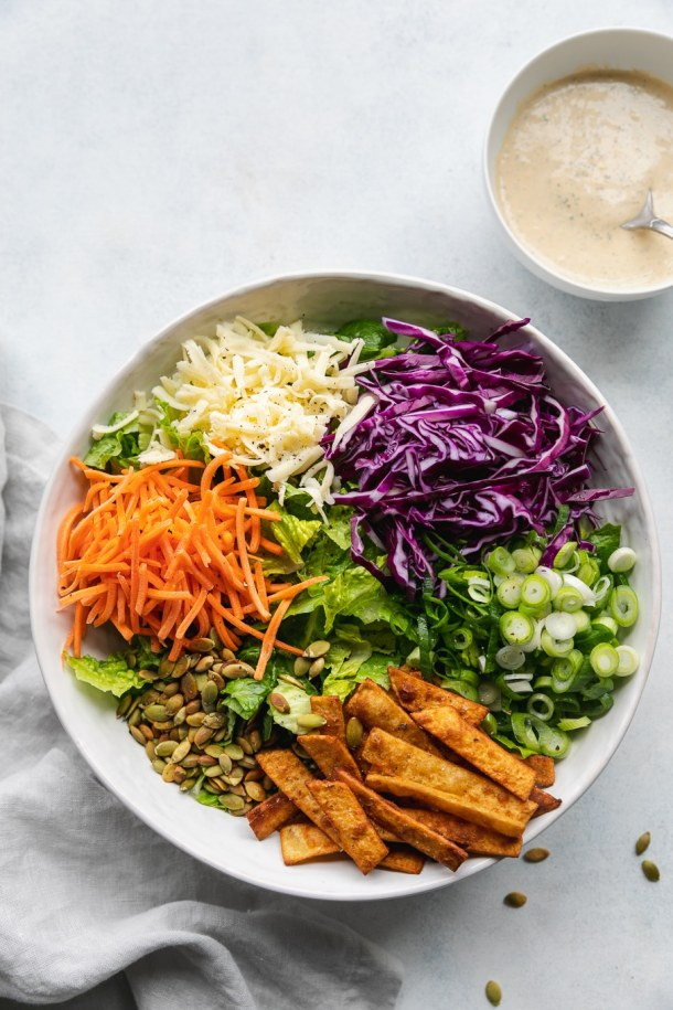 Overhead shot of a large mixing bowl filled with chopped romaine, shredded carrots, shredded white cheddar, shredded red cabbage, scallions, and tortilla strips
