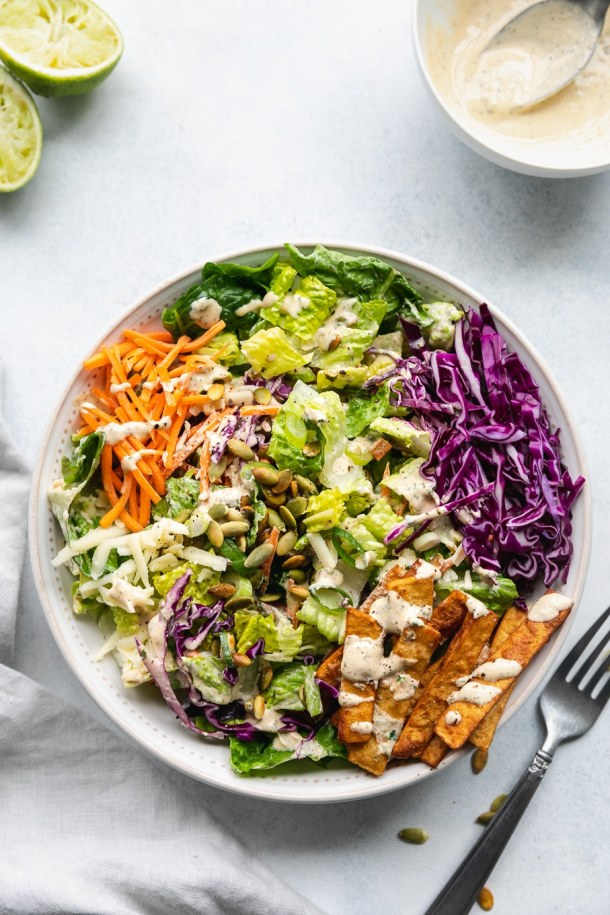 Overhead shot of a bowl of chopped salad with red cabbage, carrots, tortilla strips, and sriracha ranch dressing with a fork next to the bowl