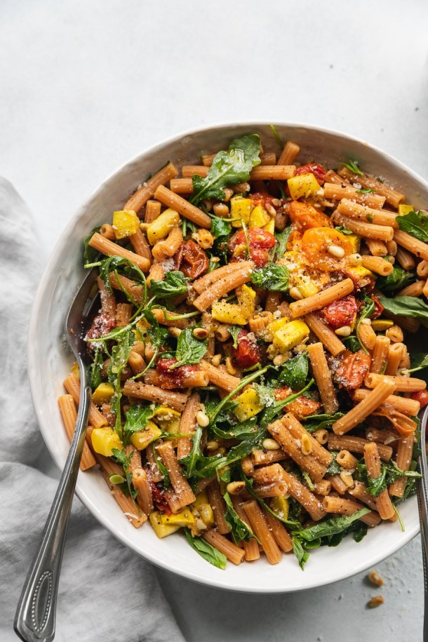 Overhead shot of a bowl of pasta filled with roasted tomatoes, summer squash, arugula, and parmesan cheese