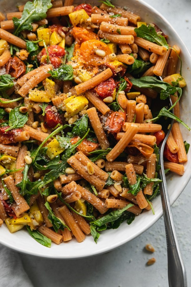 Overhead close up shot of a bowl of pasta filled with roasted tomatoes, summer squash, arugula, and parmesan cheese