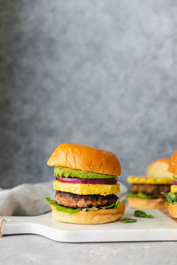 Forward facing shot of a burger with pineapple, red onion, and avocado