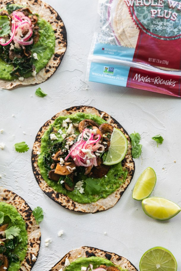 Overhead shot of tacos with green avocado sauce, pickled red onions, lime wedges, and a package of tortillas in the top right