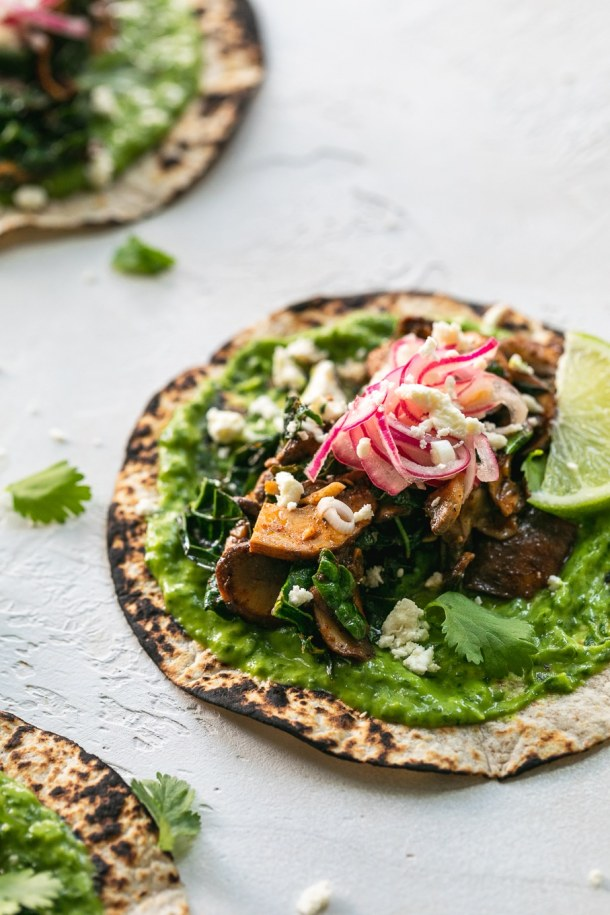 Close up shot of a mushroom kale taco with avocado cilantro sauce and pickled red onions