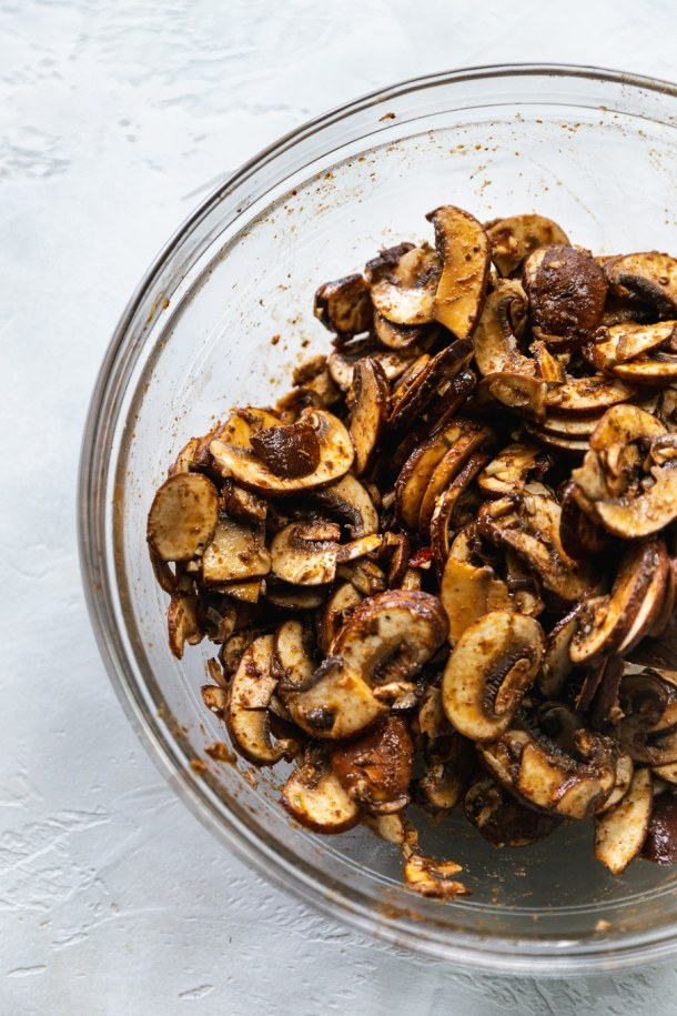 Overhead shot of a clear mixing bowl filled with marinated mushrooms