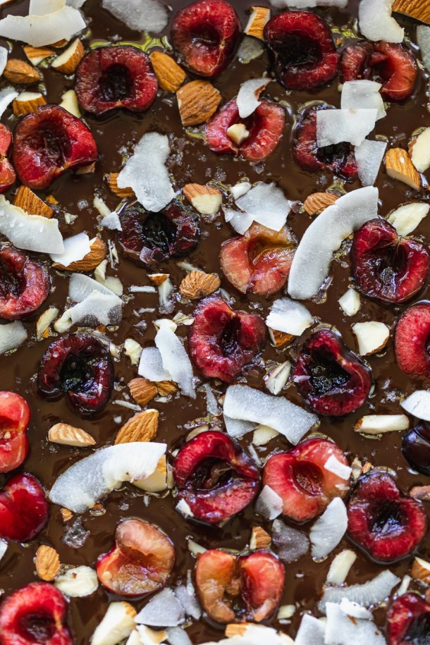 Overhead close up shot of bars with melted chocolate, halved cherries, almonds, and coconut