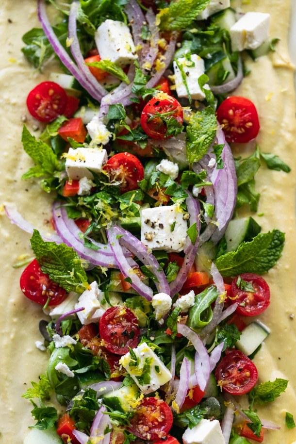 Overhead close up shot of greek salad hummus board
