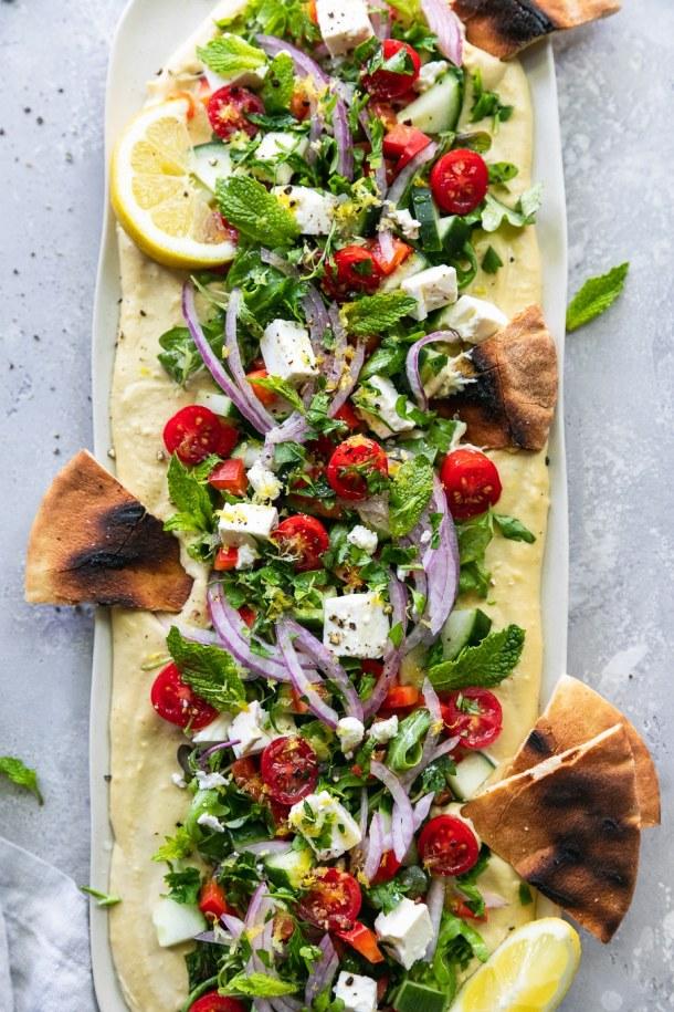 Overhead shot of greek salad hummus board with grilled pita wedges