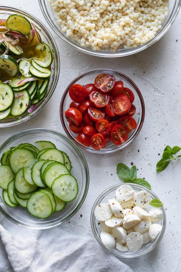 Overhead shot of bowls of couscous, marinated zucchini, cherry tomatoes, cucumber, and mini mozzarella balls