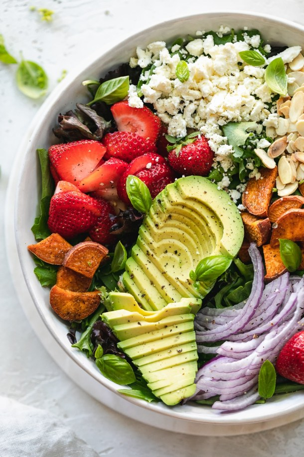 Overhead close up shot of a colorful salad with avocado, strawberries, and red onion
