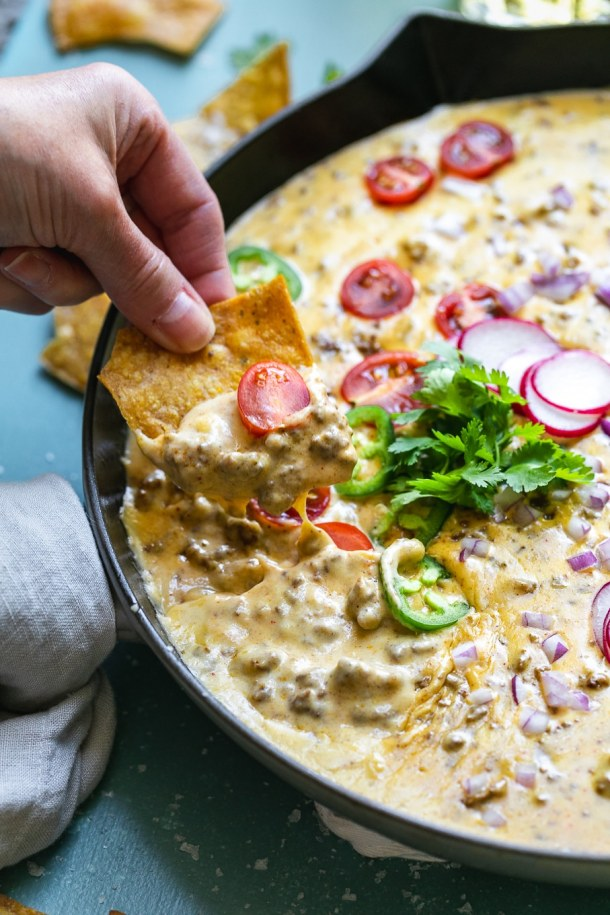 Close up shot of a hand dipping a chip into a skillet of taco beer cheese dip