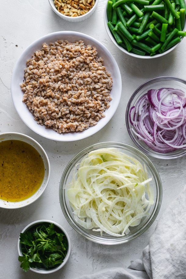 Overhead shot of bowls filled with pine nuts, red onion, green beans, and fennel