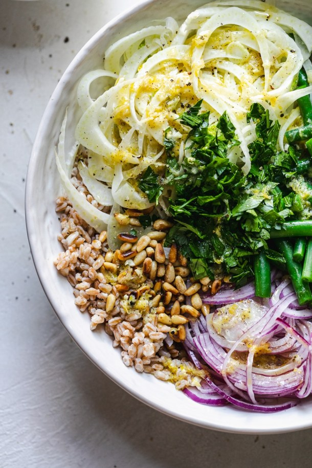 Close up shot of a bowl filled with pine nuts, red onion, green beans, and fennel