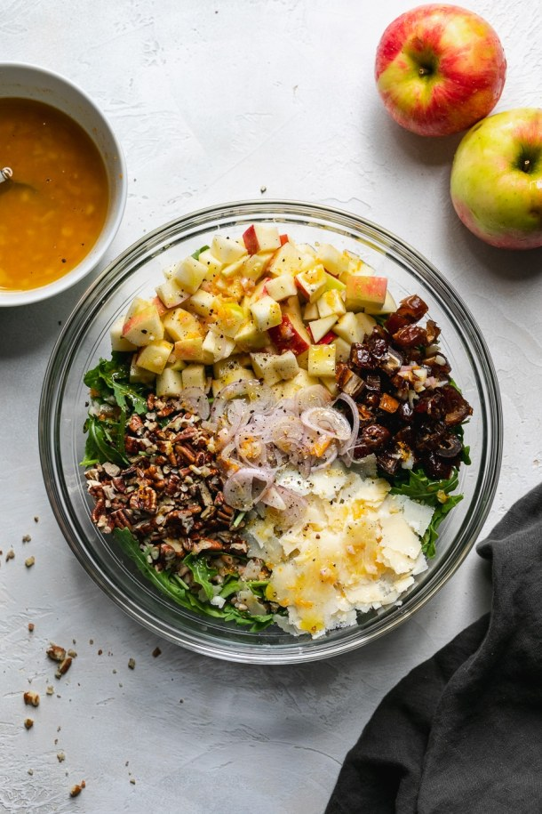 Overhead shot of a bowl filled with arugula and piles of pecans, parmesan, apples, and dates