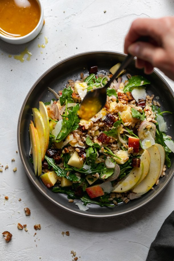 Overhead shot of a colorful apple salad being drizzled with vinaigrette