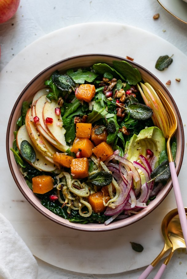 Overhead shot of a colorful fall salad with a pink and gold fork resting in the bowl
