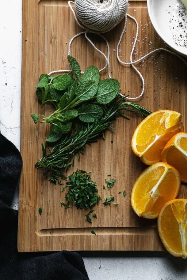Overhead shot of a wooden cutting board with orange slices, twine, and herbs