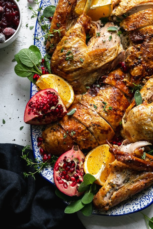 Overhead close up shot of a platter filled with turkey, herbs, pomegranate, and oranges