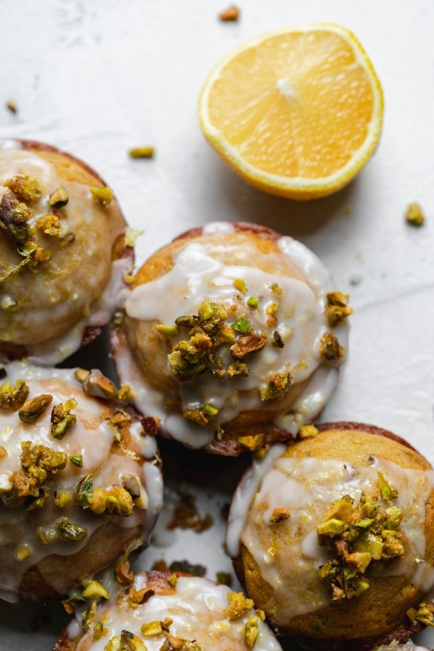 Overhead close up shot of lemon pistachio muffins with glaze and candied pistachios