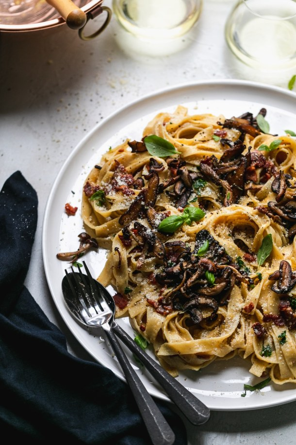 45 degree angle shot of pasta with mushrooms and herbs with a fork and spoon resting on the plate