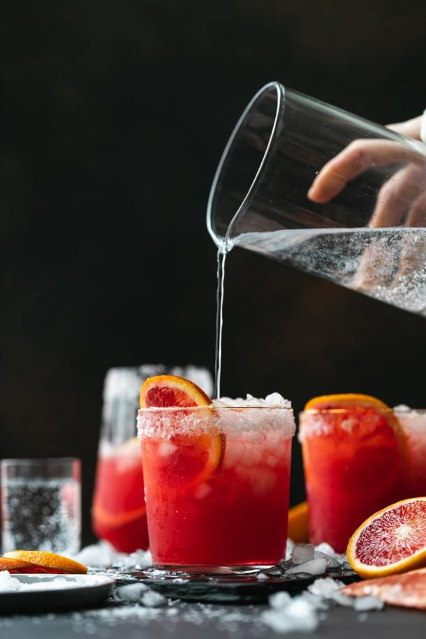 Straight on shot of a hand pouring soda water into a cocktail