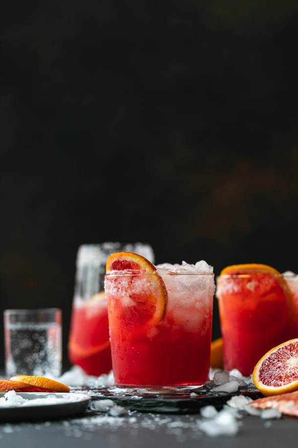 Straight on shot of blood orange paloma cocktails against a dark background