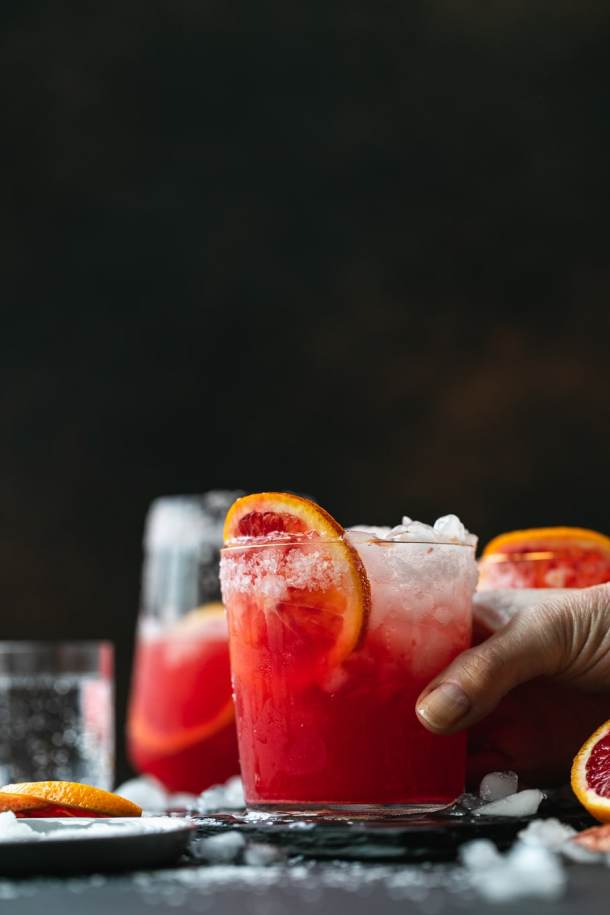Straight on shot of a hand reaching out to grab a cocktail with a blood orange slice