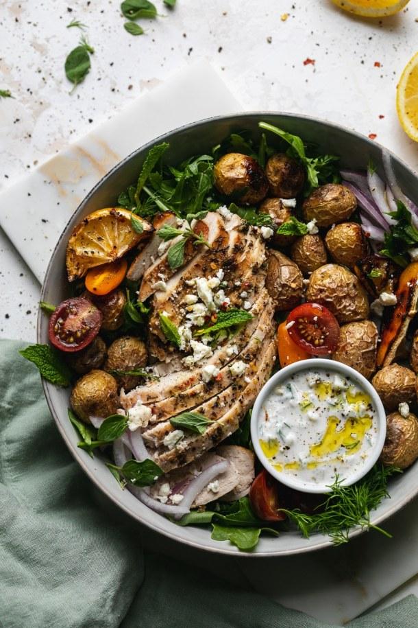 Overhead close up shot of a bowl of chicken, potatoes, tomatoes, lemon, arugula, herbs, and tzatziki sauce