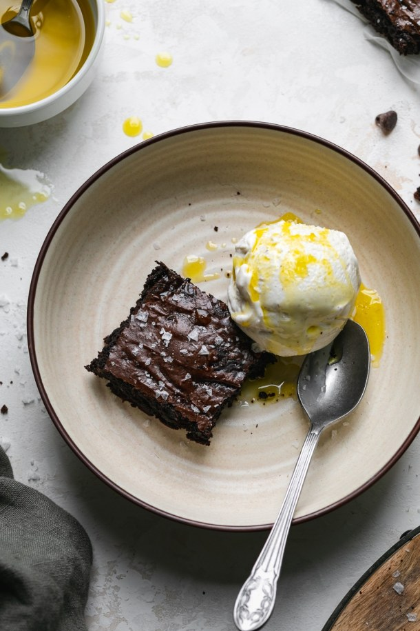 Overhead shot of a brownie and a scoop of ice cream in a bowl with a spoon