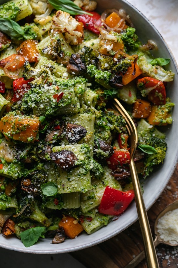 Very close up shot of a bowl of pesto pasta with veggies and a fork in the bowl