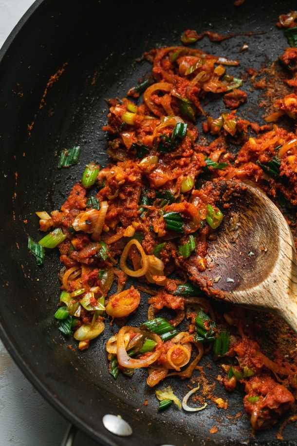 Close up shot of a skillet with red curry paste, shallots, and scallions