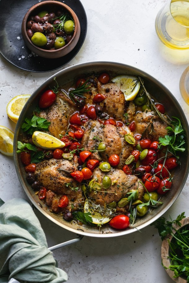 Overhead shot of a skillet filled with chicken, tomatoes, olives, herbs, and lemon