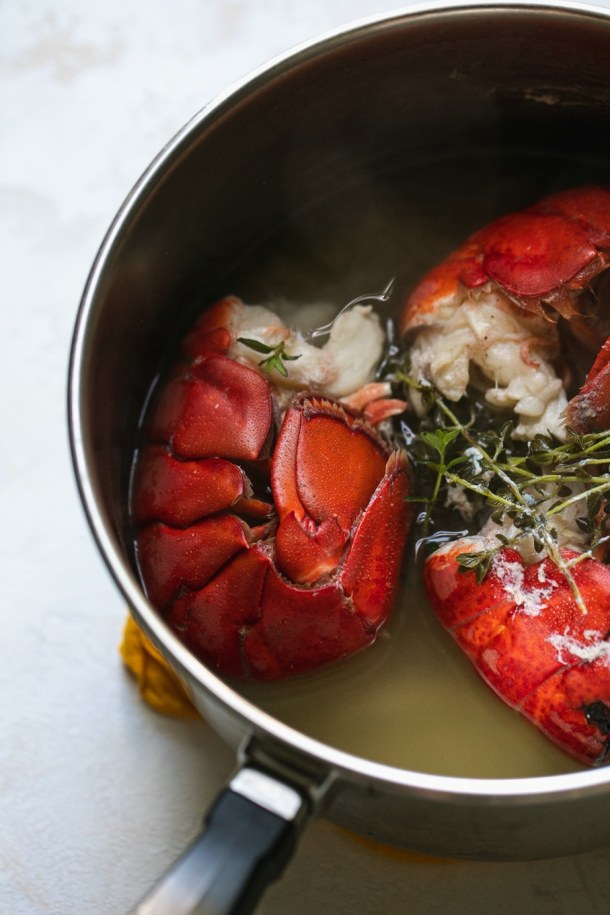 Close up shot of a saucepan with three lobster tails, white wine, and thyme