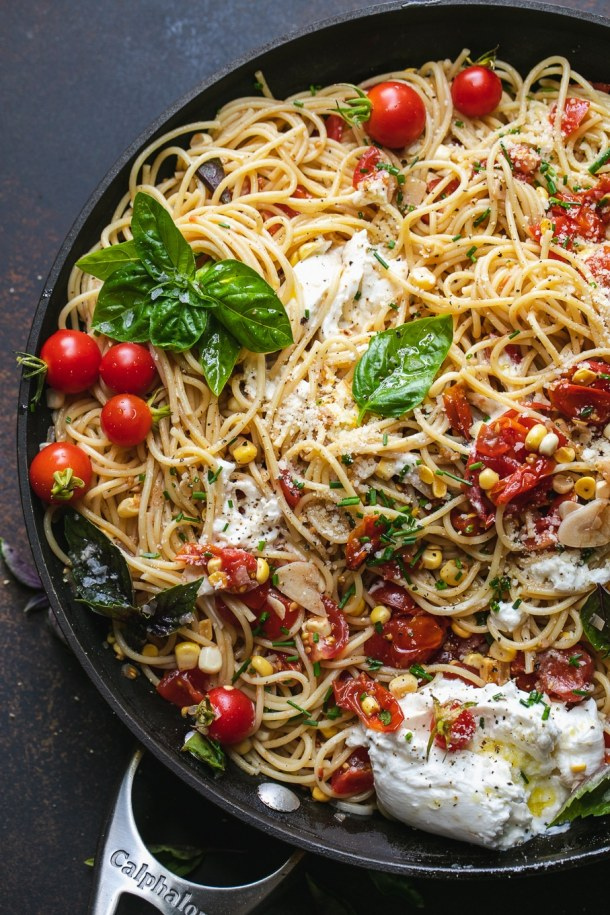 Skillet filled with pasta, tomatoes, corn, basil, and burrata