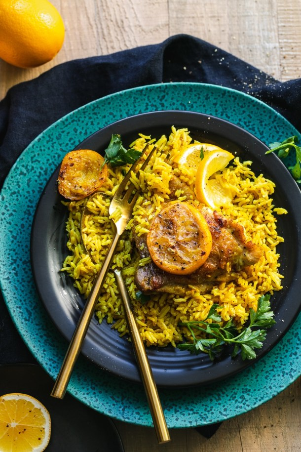 Overhead shot of a plate of golden rice and chicken with meyer lemons