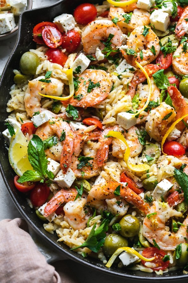 Close up shot of a cast iron skillet filled with shrimp and orzo