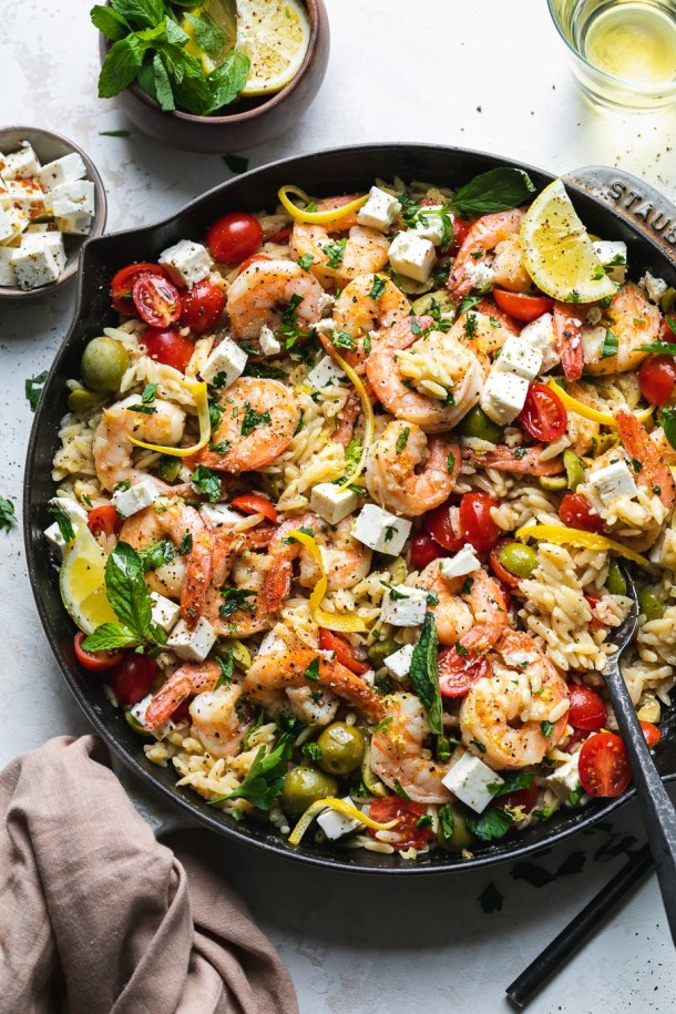 Overhead shot of a pan of orzo with shrimp, tomatoes, herbs, feta, and lemon