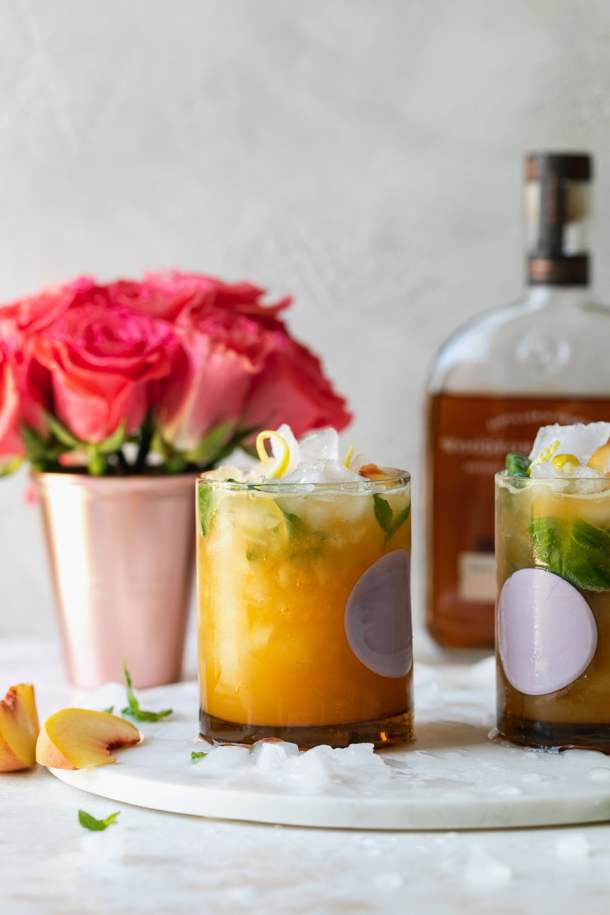 Straight on shot of two cocktails with roses and a bottle of bourbon